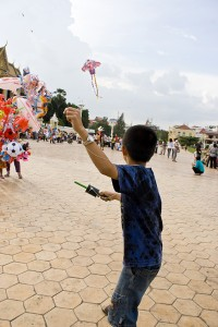 Kid flying a kite near the Cambodian Royal Palace