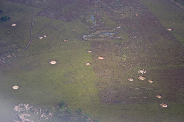 Bomb crater scars viewed from the air upon approach to Phonsavan